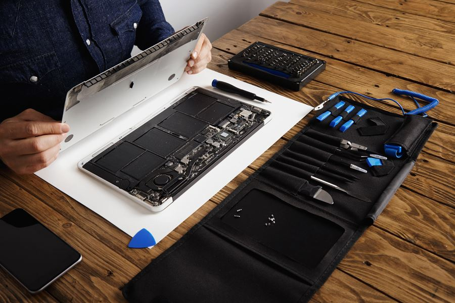 computer technician opening laptop cover using his tool kit