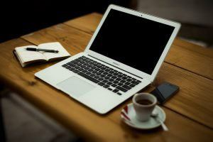 laptop and notebook and cup of coffee on a table